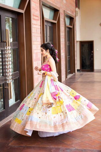 Bride twirling around in her multi-coloured lehenga.