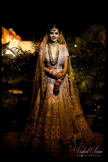 light pink bridal lehenga with contrasting green jewellery and waistbelt