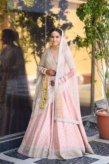 A bride in a blush pink lehenga with golden kalire