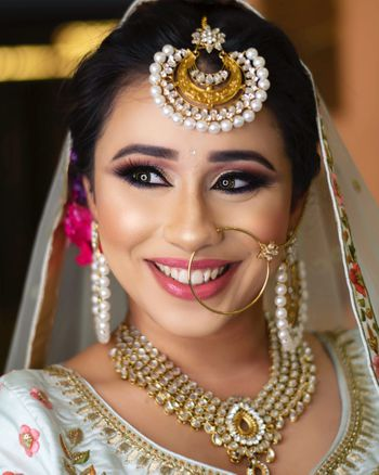 A happy bride in subtle makeup and gold jewellery.