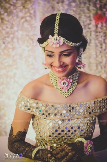 A to-be-bride in an off-shoulder top and floral jewellery on her mehndi ceremony