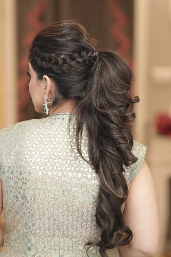 A curly ponytail hairdo with a crown braid
