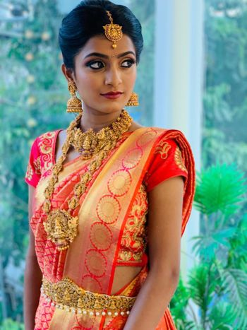 A bride in a jewel tone kanjeevaram with gold temple jewellery