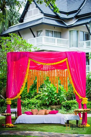 Bright pink mandap seating with genda phool decor