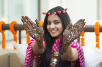 Bridesmaid wearing floral crown showing off mehendi