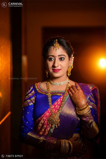 South Indian bride wearing a pink and blue saree.