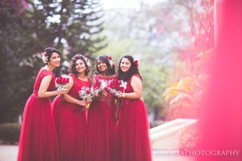 Color co-ordinated Christian bridesmaids wearing plum color gowns