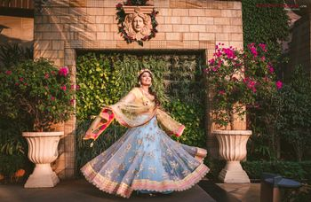 Photo of A bride in a blue net lehenga twirling on her mehndi day