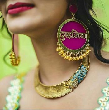 A bride flaunts her quirky dulhaniya earrings on her mehndi