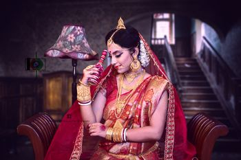 Bengali bride in red saree and gold jewellery.