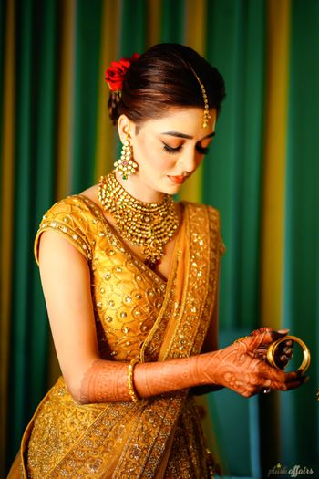 A bride in a golden lehenga getting ready
