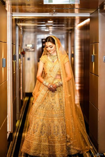 A bride in a gold lehenga