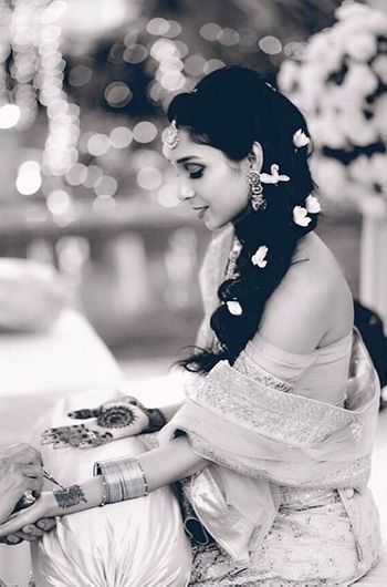 Black and white bridal portrait of bride getting mehendi put