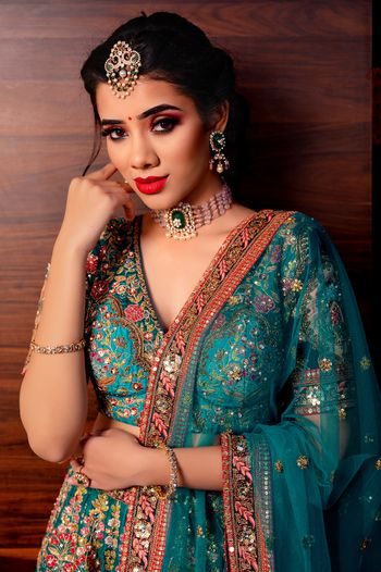 Bride in off-beat jewelry and blue embroidered lehenga.