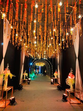 Entrance walkway decorated with sequinned strings, bulbs and floral vases.
