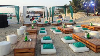 Long table seating with cushions at beach wedding