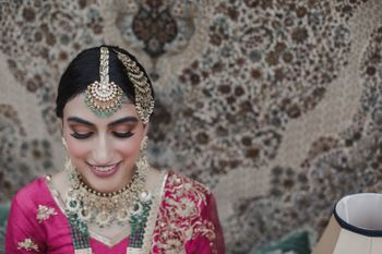 Bride wearing pink outfit with contrasting jewellery in green.