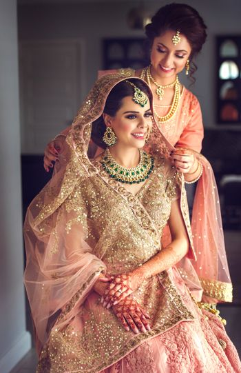 Bride with sister placing dupatta on head