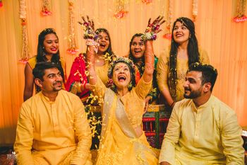 A bride in a yellow outfit and floral tiara for her mehendi