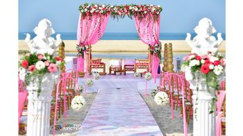 Photo of A draped beachside mandap in pink.