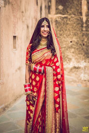 A bride in a red and gold benarasi saree on her wedding day