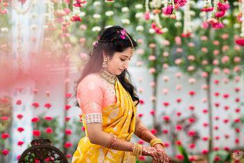 A bride in a yellow and peach silk saree