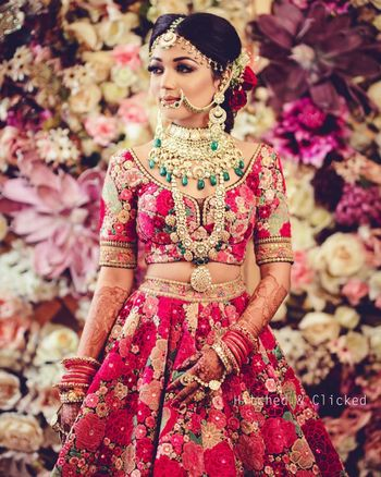 bride wearing sabyasachi bridal lehenga with layered polki necklaces