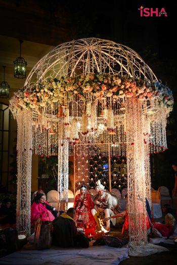 round mandap with hanging floral strings and iron structure