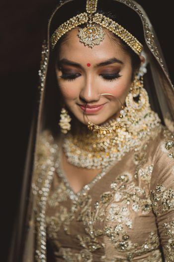 Close up shot of a bride in gold lehenga.