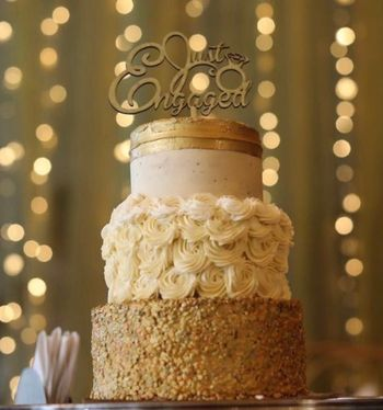 A gold and white three tier cake for engagement