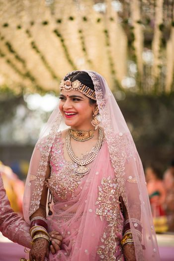 unique bridal maangtikka with pastel pink lehenga