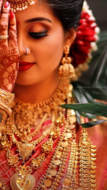 A bride wearing gold eye makeup and red lips on her wedding day