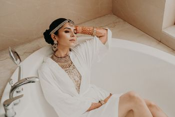 Photo of bridal getting ready shot idea in robe sitting in bathtub