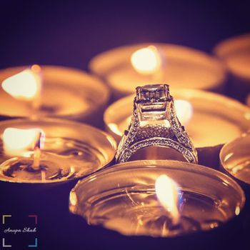 Engagement ring photographed with candles