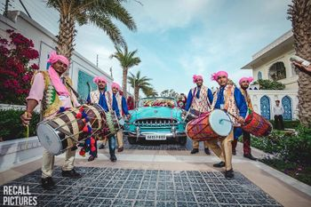 unique baraat idea with groom entering in bright vintage car