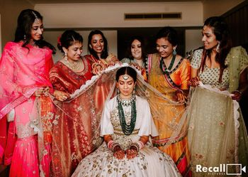 Photo of bride with her bridesmaids placing dupatta on her head