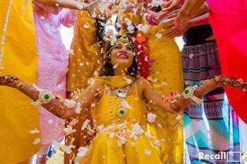Photo of bridal haldi photo idea with flower shower
