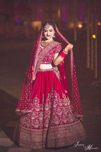Photo of Bride in deep red bridal lehenga holding dupatta