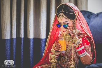 Bride in Red Lehenga Drinking Juice wearing Sunglasses