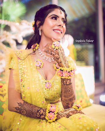 Photo of Bride in yellow mehendi lehenga and floral jewellery