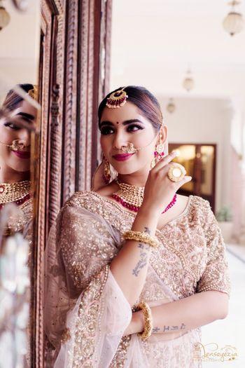 Bride wearing embellished golden lehenga with contrasting jewellery.