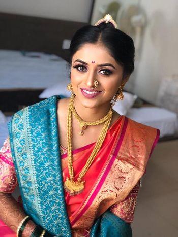 Marathi bride wearing a pink bridal saree with blue shela.
