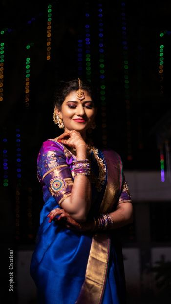 South Indian bride wearing a royal blue saree with a purple blouse.