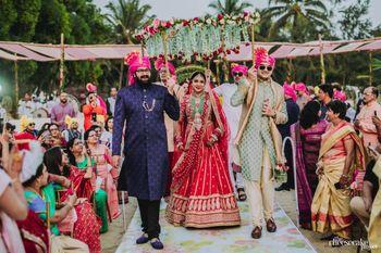 Bride in red entering under green chadar