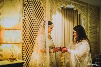 Sister helping bride wear jewellery