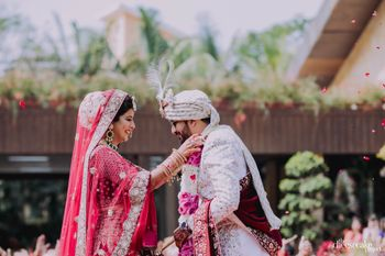 Bride and groom exchanging jaimalas.