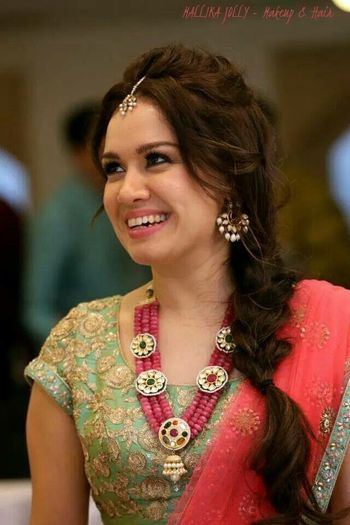 Bride on mehendi with side braid and stone necklace