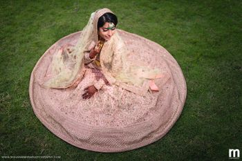 Bride sitting with pastel pink lehenga flared out