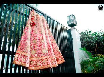 Bright Pink Lehenga with Red Border on Hanger on Gate