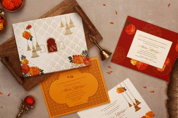 Photo of Wedding card with temple bell and marigold design